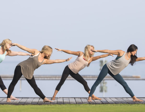 Four women in leggings doing synchronized stretching