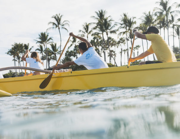 Three people wearing Camp Manitou shirts and one man wearing Alaka'i Nalu shirt rowing in the ocean with coconut trees in the background