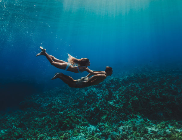 Woman holding onto shoulders of a man swimming under water