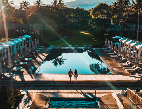 Aerial view of Beach Tree Spa and two people walking up the steps to the Lap Pool with view of Hualalai mountain beyond trees