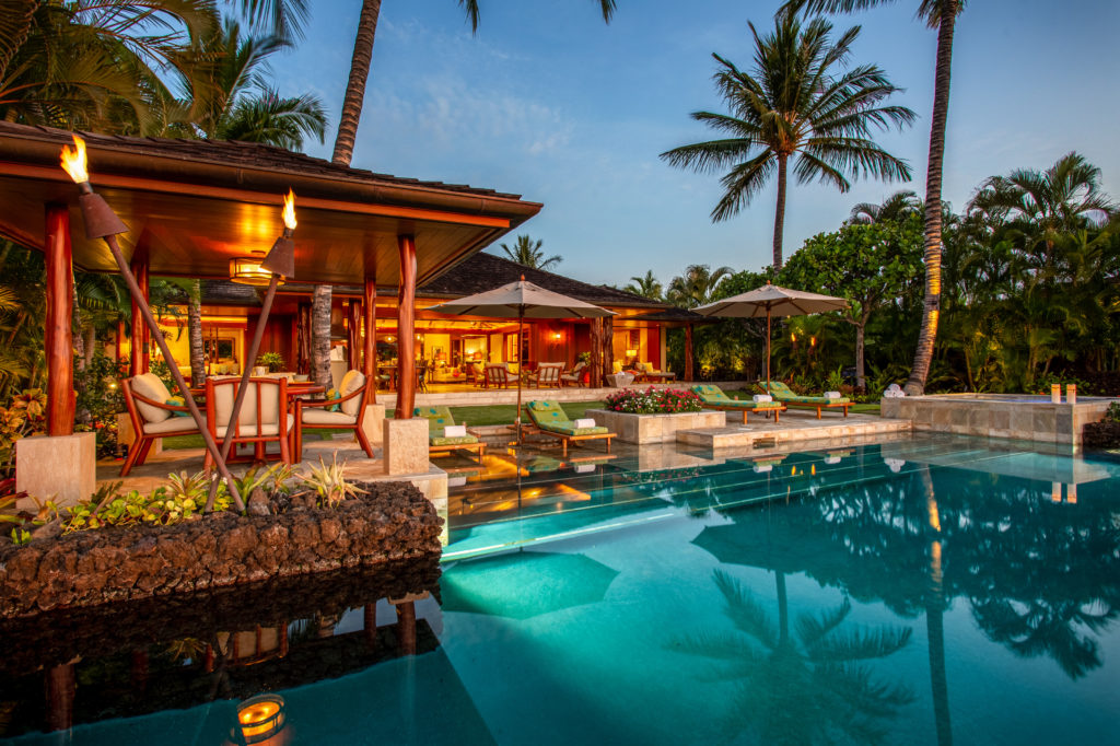 Laueki private residence looking over infinity toward outdoor seating and into lit up house, coconut trees reflecting on the water at Hualalai Resort