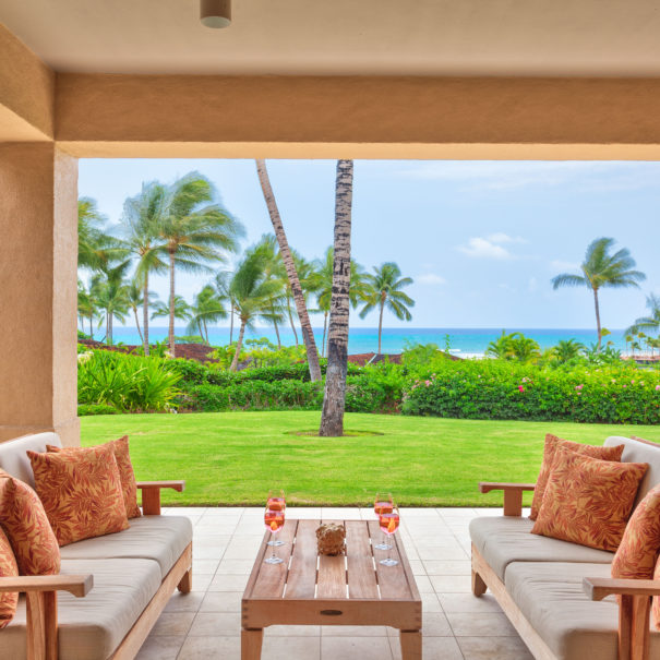 Outdoor lanai with stylish outdoor furniture with warm colored pillows facing each other over a table with wine glasses in front of a green lawn with ocean views in the background.