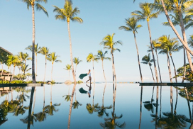 Woman walking at the edge of an infinity pool at FOUR SEASONS with sarong blowing behind and coconut trees reflected in the water