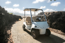 Golf cart on path with lava rock walls and Hualalai mountain in the background