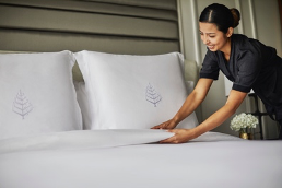 Four Seasons housekeeper making a white bed