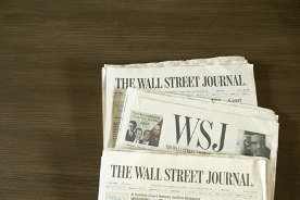 Three issues of the Wall Street journal on a wooden background